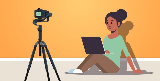African american woman blogger using laptop recording video blog with digital camera on tripod live streaming social media blogging concept full length horizontal