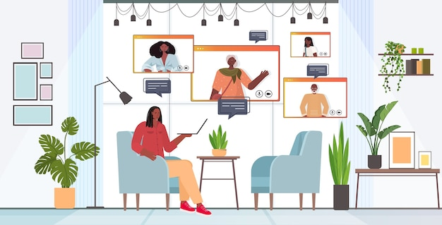 화상 통화 온라인 통신 개념 거실 인테리어 수평 동안 웹 브라우저 창에서 가족 구성원과 가상 회의를 갖는 아프리카 계 미국인 여자