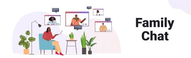Афро-американская женщина, имеющая виртуальную встречу с членами семьи в окнах веб-браузера во время видеозвонка, концепция онлайн-общения, интерьер гостиной, горизонтальный
