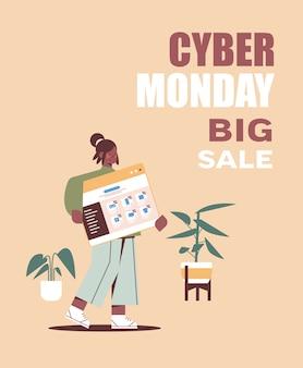 Афроамериканка женщина держит окно веб-браузера интернет-магазины кибер понедельник большая распродажа праздничные скидки концепция электронной коммерции вертикальный