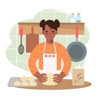 台所でアフリカ系アメリカ人の女性がふわふわのパンを準備します彼女は手に生地を持っています