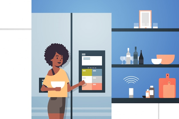 African american woman touching refrigerator screen with smart speaker voice recognition