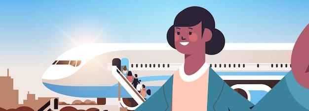 Афро-американская женщина-путешественница, делающая селфи на камеру смартфона девушка делает селфи возле самолета горизонтальный портрет векторная иллюстрация
