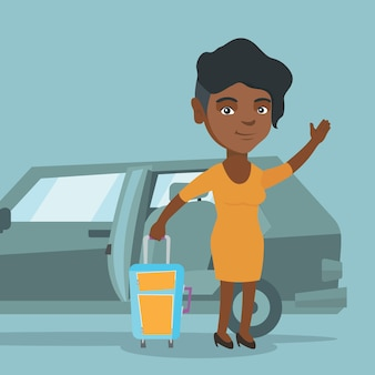 African-american woman waving in front of car.