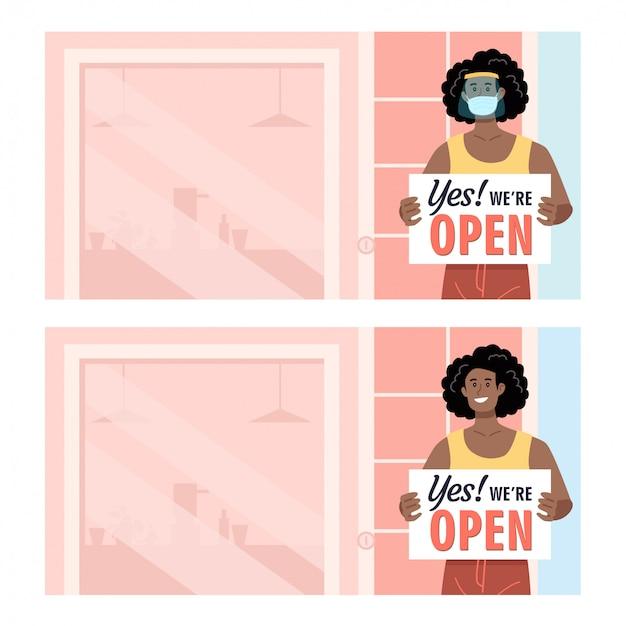 彼女の店の前にオープンサインを保持している保護を身に着けているアフリカ系アメリカ人の女性