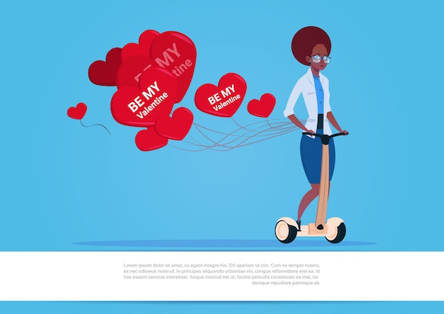 African american woman with heart shaped air balloons riding electric scooter happy valentine day concept