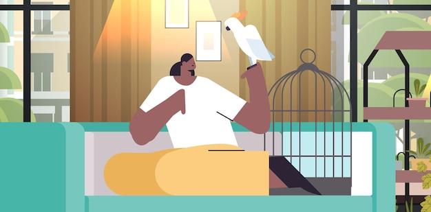 Афро-американская женщина с девушкой-попугаем заботится о домашнем животном, птице, интерьере гостиной