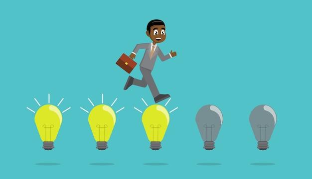 アフリカのビジネスマンは、電球でジャンプします。