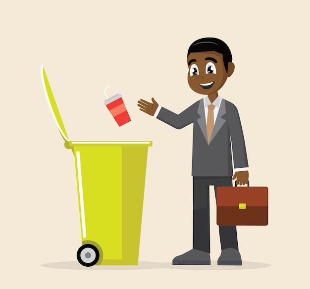 아프리카 사업가 쓰레기통에 쓰레기를 던져.