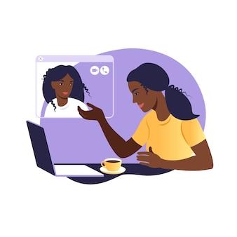 Африканские подруги общаются онлайн. девушка сидит в кресле перед ноутбуком и разговаривает с другом