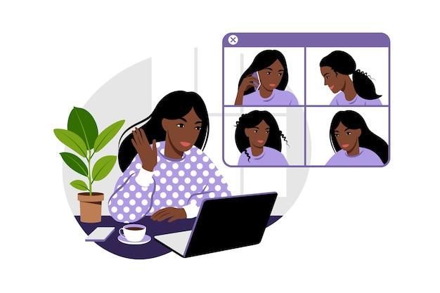 アフリカのガールフレンドはオンラインでチャットします。ノートパソコンの前の椅子に座って友達と話す女の子