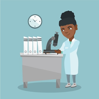 African laboratory assistant with a microscope.