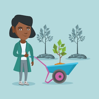 African woman pushing wheelbarrow with plant.