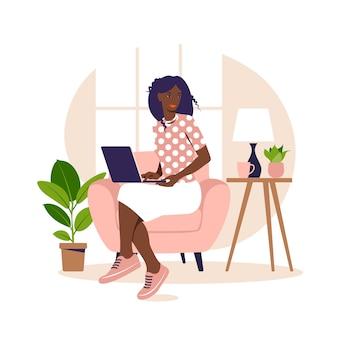 ノートパソコンで肘掛け椅子に座っているアフリカの女性。コンピューターでの作業。