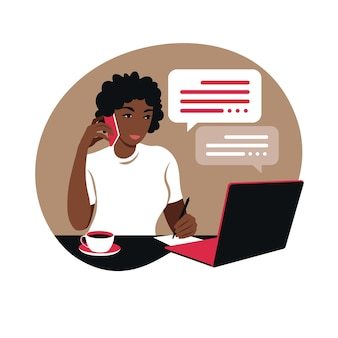 African woman works on a laptop computer and talks on the phone sitting at a table at home with a cup of coffee and papers.
