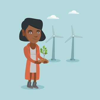 African worker of wind farm holding small plant.