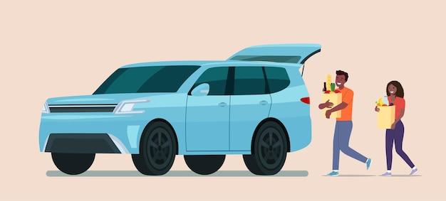 アフリカ系アメリカ人の男性と女性は車で食料品の袋を運びます。