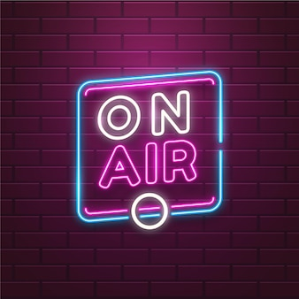 On air sign with neon frame on brick wall