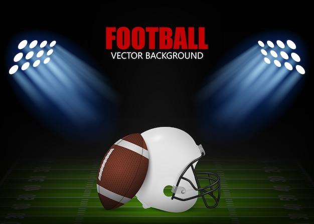 アメリカンフットボールの背景-投光照明で照らされたフィールド上のヘルメットとボール。