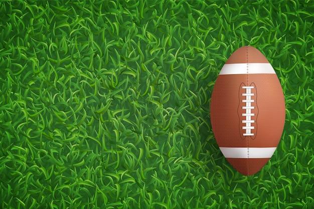 American football ball on green grass texture background.