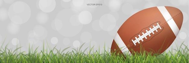 Мяч для американского футбола на поле зеленой травы с легким размытым фоном боке