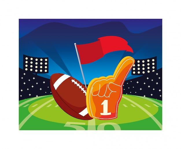 American football ball with hand glove on stadium grass