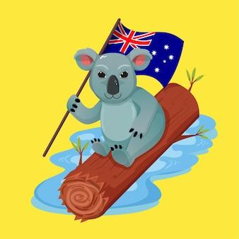 호주 코알라가 호주 국기를 들고 물 위에 떠있는 나무를 기어 오르고 있습니다. 행복한 호주의 날 축하