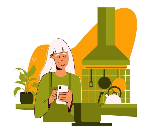 Пожилая привлекательная женщина в фартуке на кухне использует смартфон для написания или просмотра рецептов.