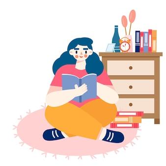 Девушка сидит на полу в комнате, читает и учится