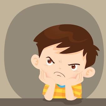 怒っている少年の顔に不満の表情を座っています。