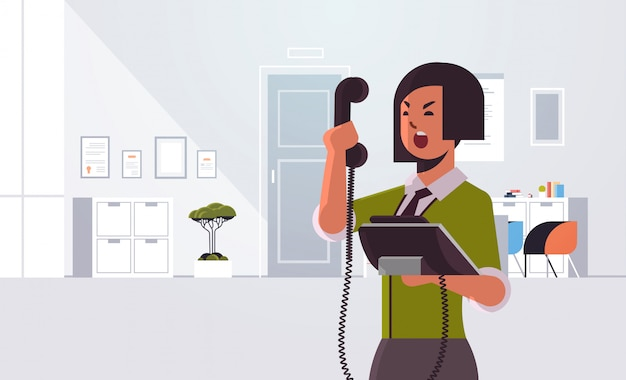 Angry businesswoman screaming at phone