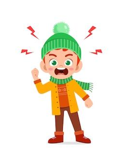 겨울철에 화난 귀여운 꼬마가 비명을 지르고 재킷을 입습니다.