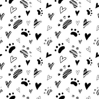 動物の猫の足とハートのパターンがシームレス