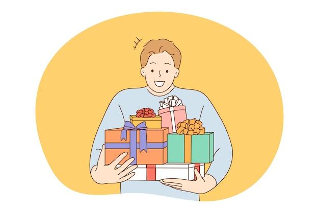 記念日、誕生日またはクリスマスプレゼント、お祝いのコンセプト。ヒープを運ぶ若い幸せな男の男