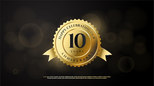 Anniversary celebration number with the number 10 in gold in a gold emblem.
