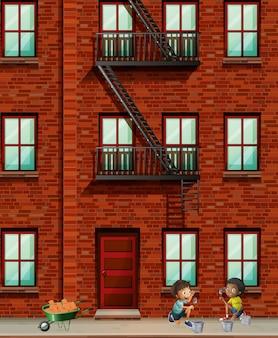 男の子がレンガを敷くアパートの建物のシーン