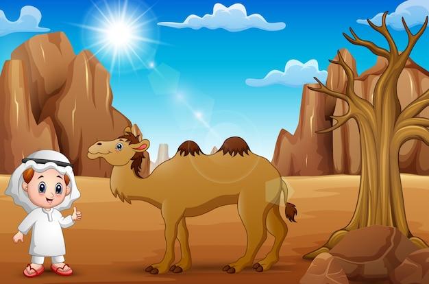 アラブ男の子は砂漠のラクダで親指を上げる