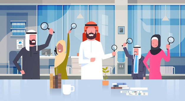 Arab business people group holding magnifying glasses in modern office team of arabic businesspeople making research