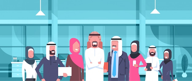 Arab businessman boss with team of arabic business people in modern office wearing traditional clothes arab employees workers