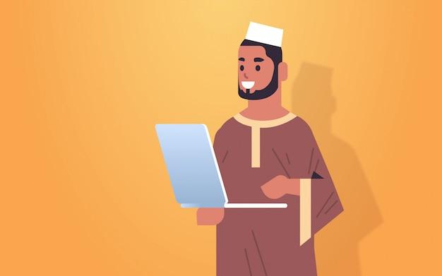 컴퓨터 응용 프로그램 세로 가로를 사용하여 공식적인 마모에 아랍어 비즈니스 남자 회사원 미소 노트북에서 작업 아랍 사업가