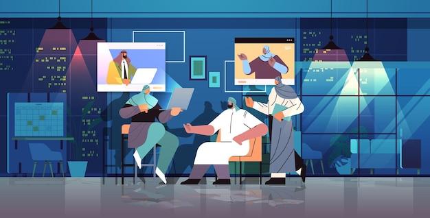Команда арабских бизнесменов обсуждает во время видеозвонка виртуальная конференция онлайн-общение концепция совместной работы ночной офис интерьер горизонтальная полная длина векторная иллюстрация