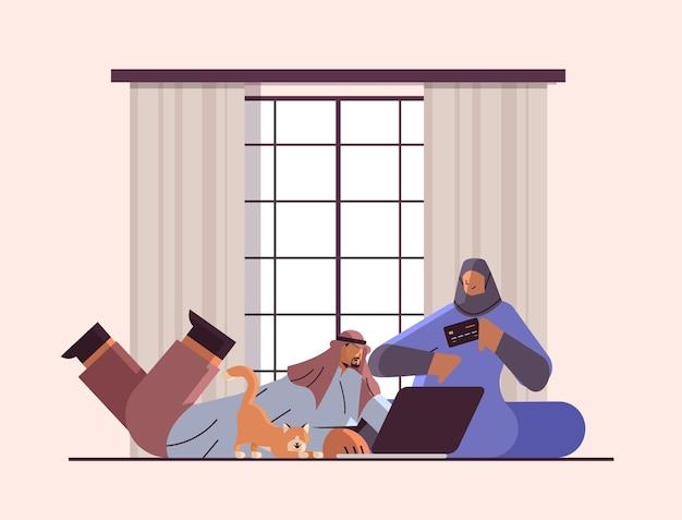 노트북 온라인 쇼핑 개념을 사용하여 신용 카드를 가진 아랍 커플 남자 여자 함께 상품 주문