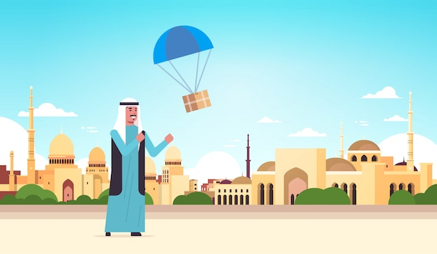 Arab man catching parcel box falling down with parachute shipping package air mail express postal delivery concept nabawi mosque building muslim cityscape background full length horizontal