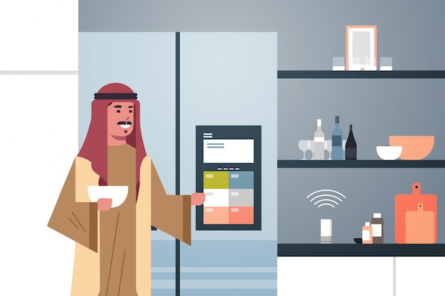 Arab man touching refrigerator screen with smart speaker voice recognition