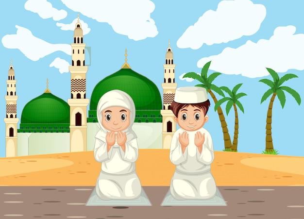 Арабские мусульманские мальчик и девочка молятся в традиционной одежде на фоне мечети
