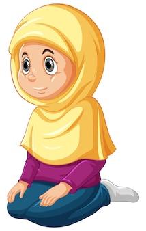白い背景で隔離の座っている位置を祈る伝統的な服でアラブのイスラム教徒の少女