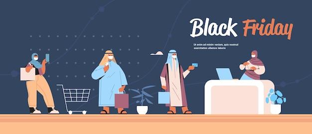 マスクをしたアラブ人が買い物袋を持って列に並んでキャッシュデスクに並んでいるブラックフライデーセールコロナウイルス検疫コンセプトコピースペース