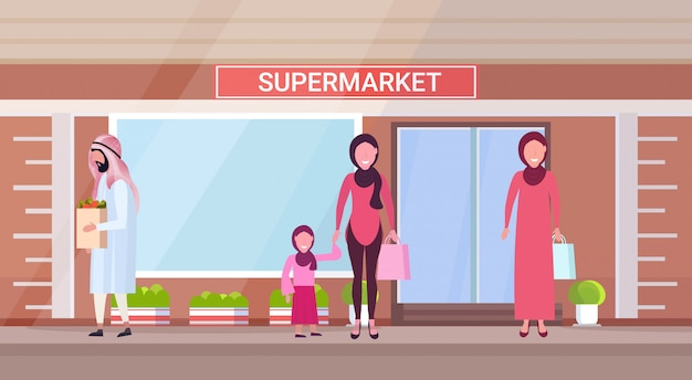 Arab people in traditional clothes holding shopping bags with groceries arabic characters standing outdoor modern grocery shop supermarket exterior horizontal