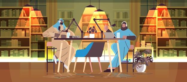 Арабские подкастеры разговаривают в микрофоны, записывая подкаст в студии подкастинга, концепция онлайн-радиовещания