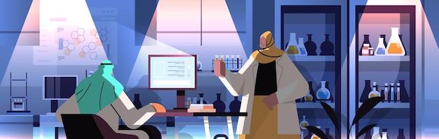 아랍 연구원 팀은 컴퓨터에서 작업하고 실험실 분자 공학에서 화학 실험을 하고 있습니다.